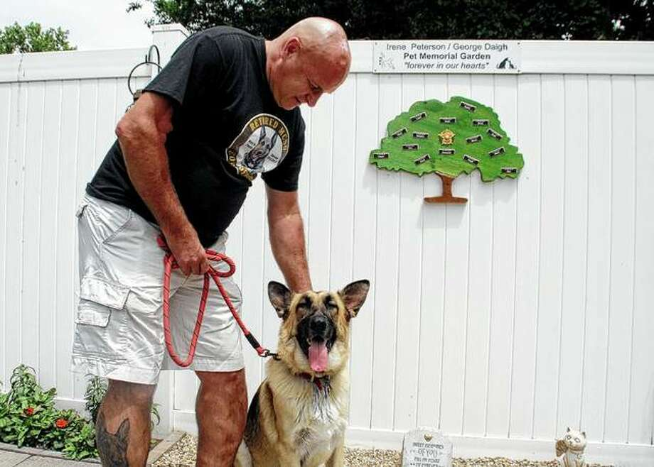 Macon County Court Security Officer Alan Engdale pets his new dog, Tazer, on Sunday in Decatur. Engdale said he just had to attend Sunday's pet memorial service and pay tribute to his late police dog, Kid. Photo: Tony Reid | Herald & Review Via AP