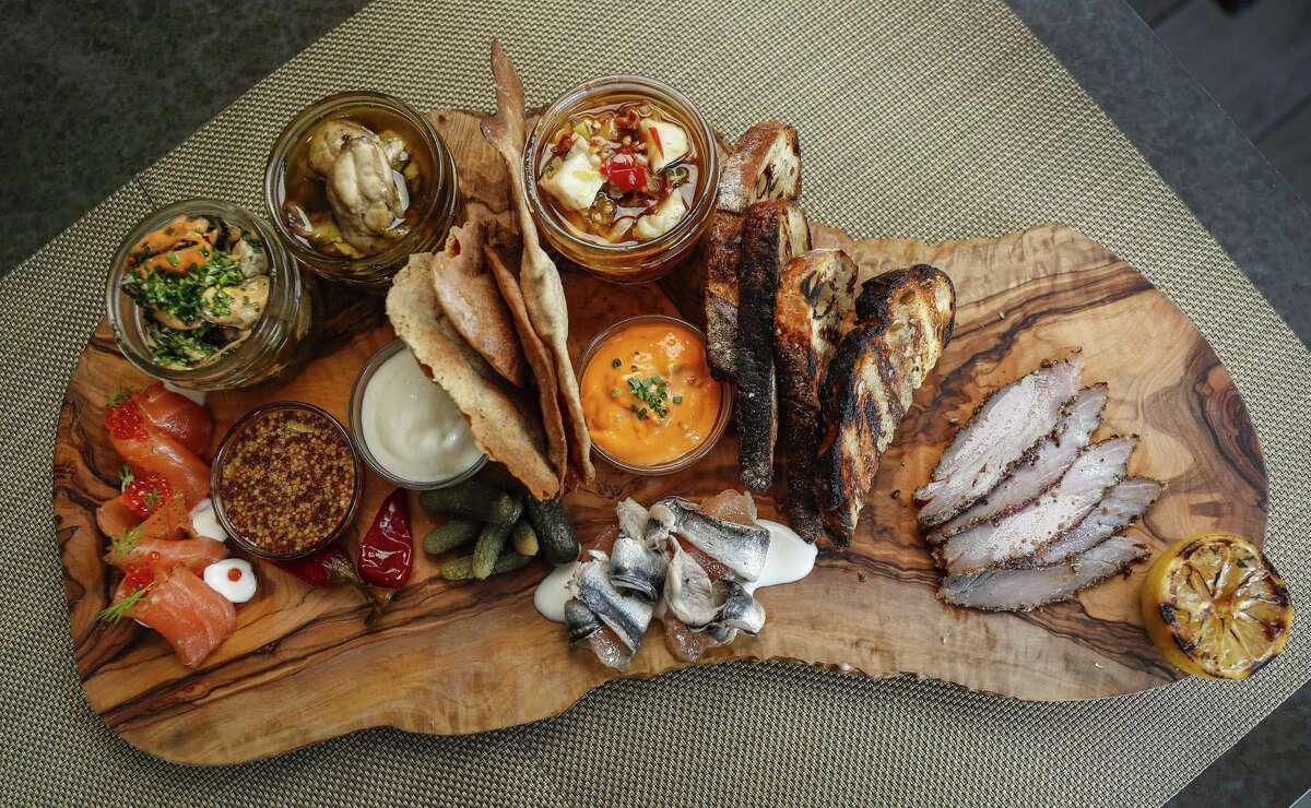 1751 Charcuterie Board with salmon gravlax, cured tuna, conserva, smoked oysters, boquerones, pickles, mostarda and toasty bread at 1751 Sea & Bar