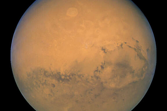 Mars is shown within minutes of the planet's closest approach to Earth in nearly 60,000 years in this image taken by NASA's Hubble Space Telescope. This image was made from a series of exposures taken between 5:35 a.m. and 6:20 a.m. EDT Aug. 27, 2003 with Hubble's Wide Field and Planetary Camera 2. After decades of watching astronauts circle Earth, space visionaries finally have reason for optimism: NASA and other agencies are working with the White House on a bold, new course of exploration. (NASA)
