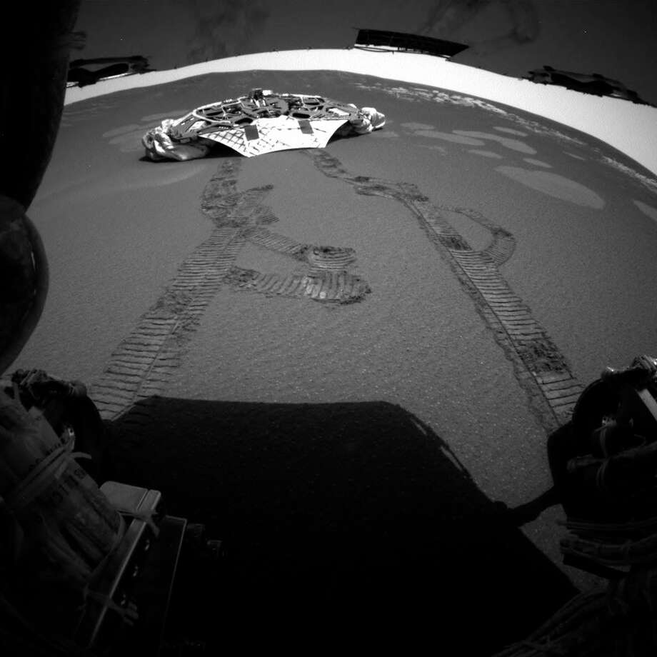 This photo released Thursday, Feb. 5, 2004 made by one of the rear hazard-avoidance cameras on NASA's Opportunity rover, shows Opportunity's landing platform, with freshly made tracks leading away from it. Opportunity rolled about 11 feet on Thursday, the first day it has moved since it left the lander on Saturday. Engineers commanded Opportunity to turn slightly during the drive, to test how it steers while rolling through the martian soil. Photo: NASA Via Associated Press / 2004 AP