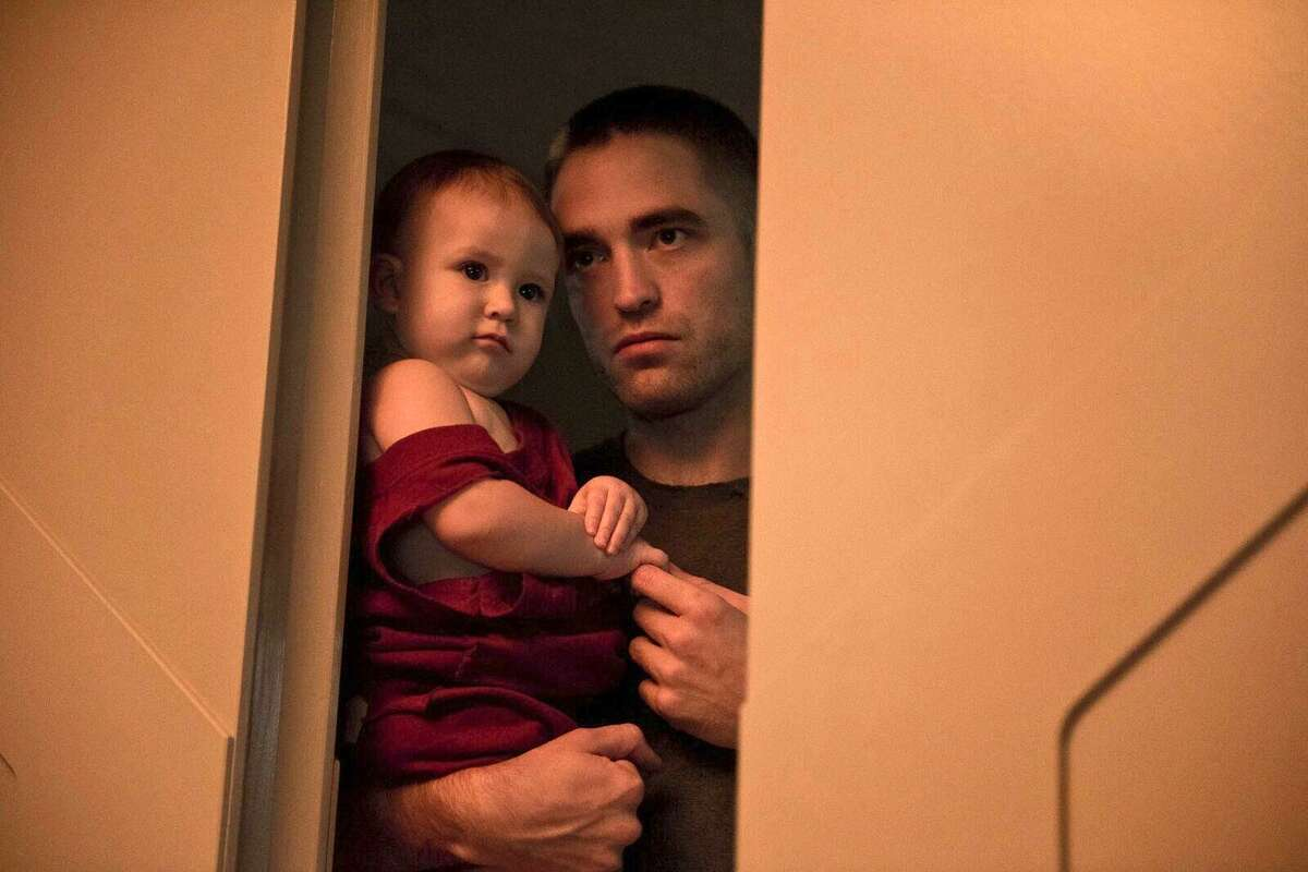 Robert Pattinson and his baby daughter are a long way from home in