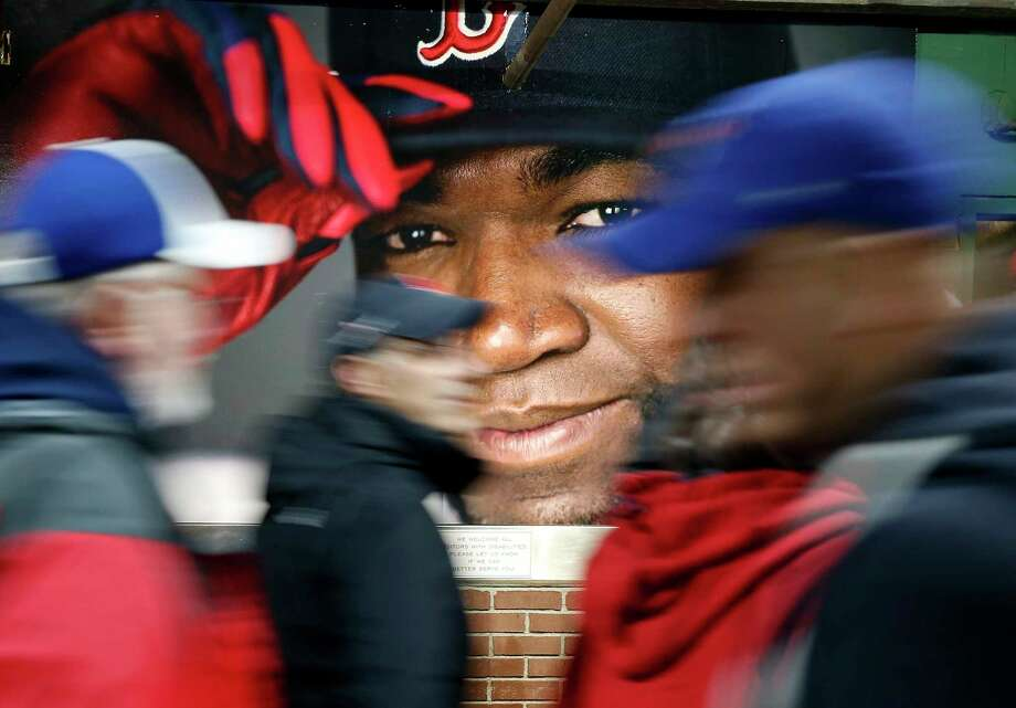 FILE - In this Oct. 1, 2016, file photo, fans at walk past a photograph of Boston Red Sox's David Ortiz before a baseball game against the Toronto Blue Jays at Fenway Park in Boston. Ortiz was back in Boston for medical care after authorities said the former Red Sox slugger affectionately known as Big Papi was ambushed by a gunman at a bar in his native Dominican Republic.