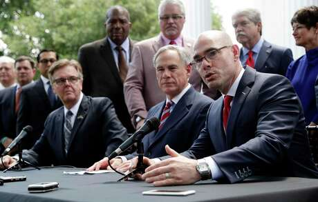 Lt. Governor Dan Patrick, seated left, and Governor Greg Abbott, seated center, listen as Speaker of the House Dennis Bonnen, seated right, answers a question during a joint news conference to discuss teacher pay and school finance at the Texas Governor's Mansion in Austin, Texas, Thursday, May 23, 2019, in Austin. (AP Photo/Eric Gay)