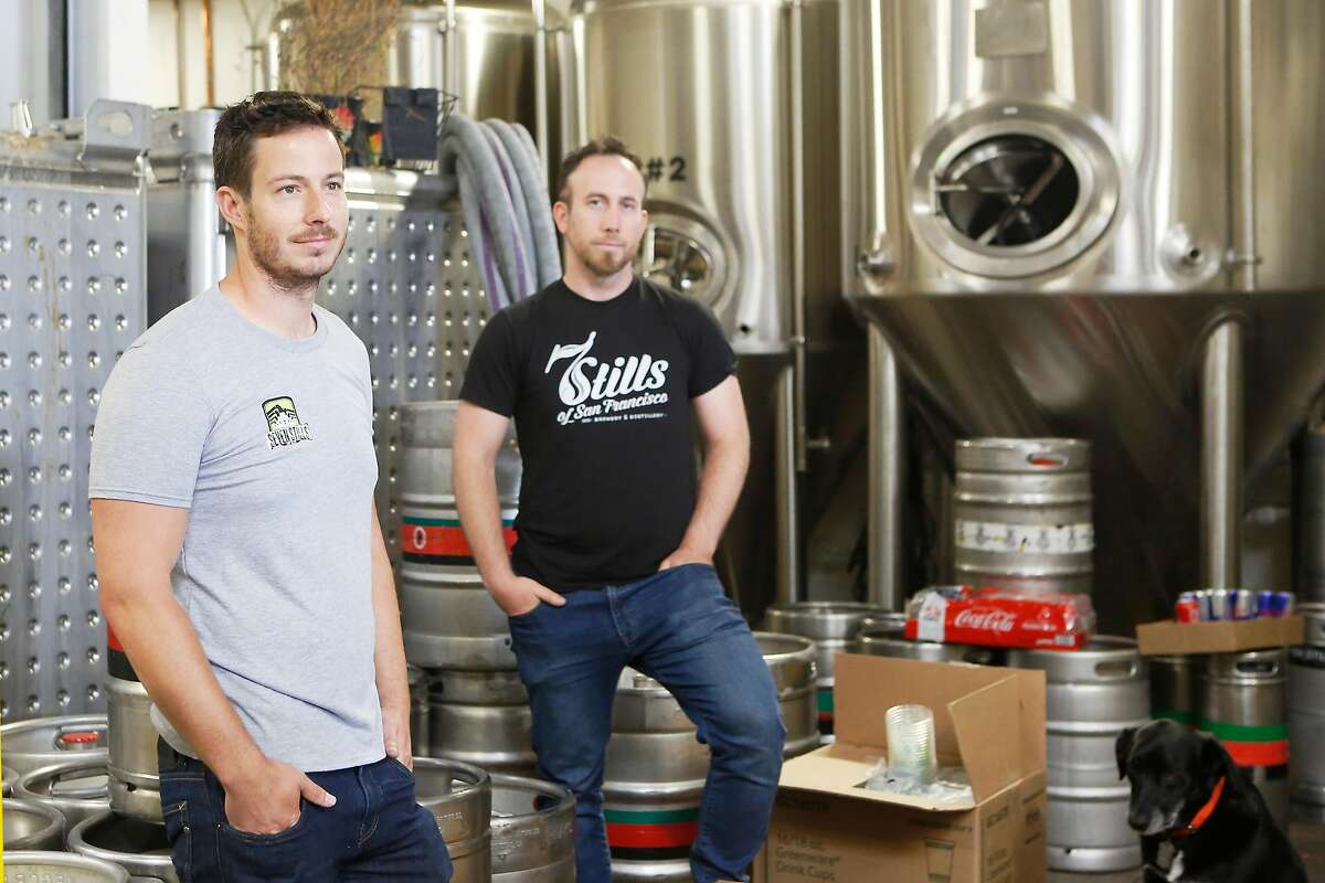 Founders Tim Obert, left, and Clint Potter, right, pose at their brewery Seven Stills on Egbert St. with pet dog Tango on Wednesday, June 20, 2018 in San Francisco, Calif. Although Seven Stills is only two years old, it's about to open its fourth location in the city.