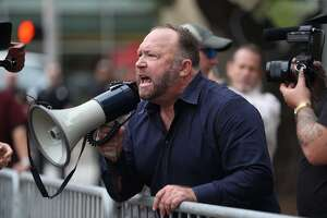 Alex Jones, of InfoWars, yells at protestors outside of Toyota Center before a Trump campaign rally, Monday, October 22, 2018, in Houston.