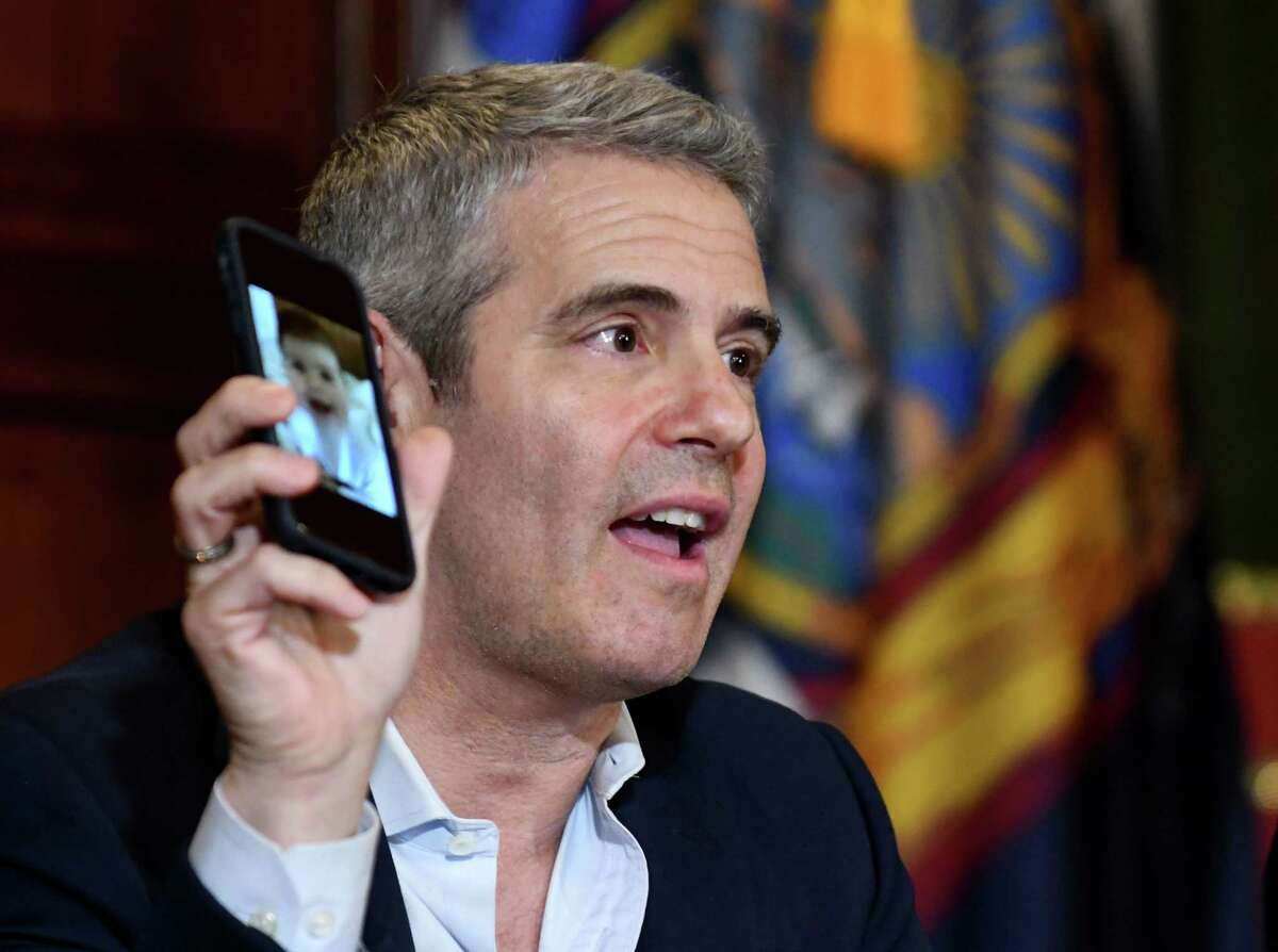 Andy Cohen, producer and surrogacy advocate, holds photo of his son while joining Gov. Andrew Cuomo in a press conference in support of the surrogacy bill on Tuesday, June 11, 2019, at the Capitol in Albany, N.Y. The bill, if passed, would bring New York in line with more than three dozen states that have legalized the practice, in which a surrogate carries a child they are not related to for someone else. New York is currently one of three states that outlaw gestational surrogacy agreements. (Will Waldron/Times Union)