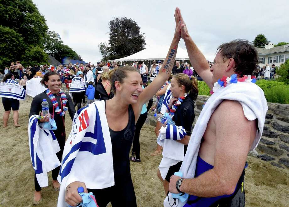 Kate Russack, of Greenwich, shares a high five with John Merrill, of Greenwich, after the two participated in the 12th annual Swim Across America Greenwich-Stamford Open Water Swim in 2018. The event returns with a new name June 22. Photo: Hearst Connecticut Media File Photo / Stamford Advocate