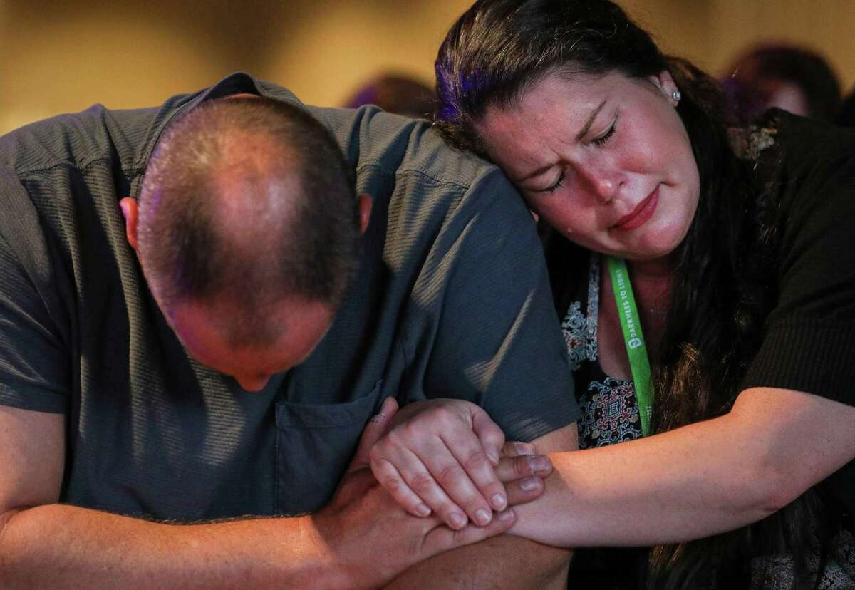 Christy Freeland, right, who said she was abused for seven years starting at the age of 8, cries while praying with her husband Kevin Freeland, during a panel discussion about sexual abuse and the Southern Baptist Convention, on the eve of the SBC's annual meeting on Monday, June 10, 2019, in Birmingham.