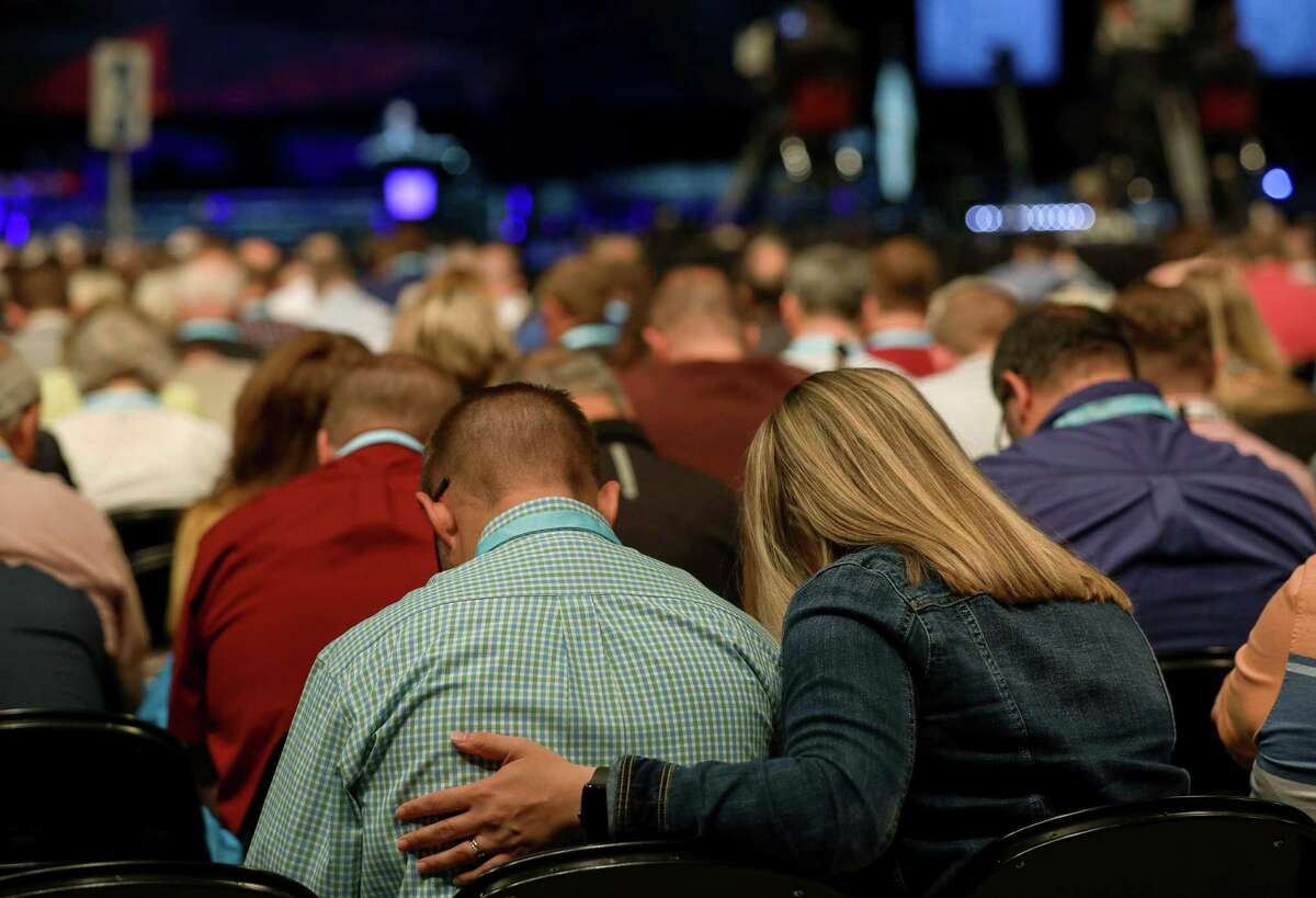 People pray before the introduction of new motions on the first day of the Southern Baptist Convention's annual meeting on Tuesday, June 11, 2019, in Birmingham.