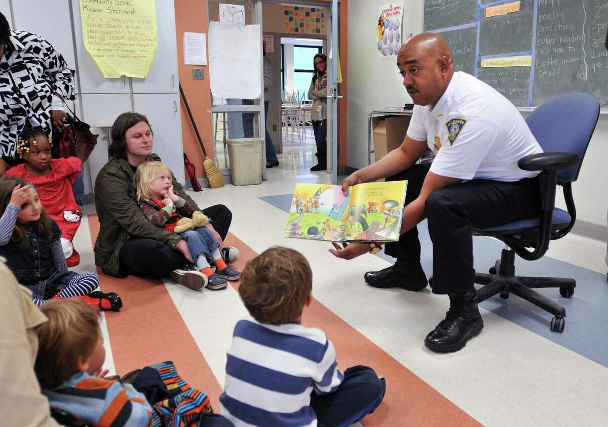 Assistant New Haven Police Chief Thaddeus Reddish reads during a free family reading event sponsored by the Edith B. Jackson child care program in 2012.
