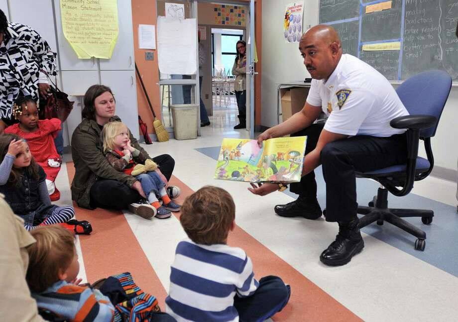 Assistant New Haven Police Chief Thaddeus Reddish reads during a free family reading event sponsored by the Edith B. Jackson child care program in 2012. Photo: Peter Casolino / Hearst Connecticut Media File Photo