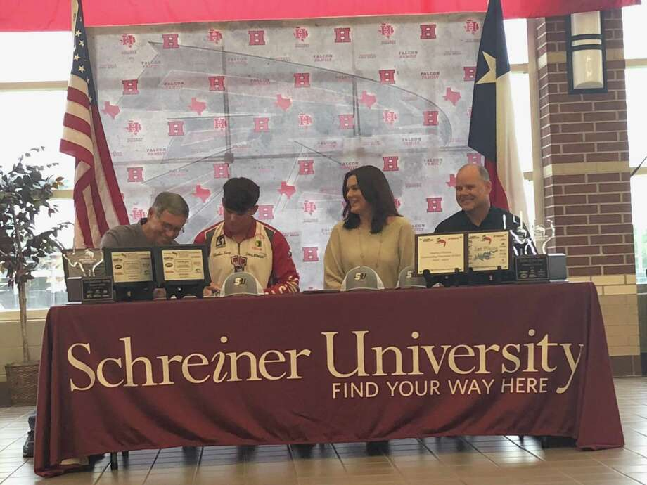 Matthew Dorcz's parents and Schreiner University bass fishing team coach Raymond Holloway look on as Matthew signs his bass fishing scholarship letter for Schreiner University at a ceremony at Hargrave High School on May 22 Photo: Elliott Lapin / Staff Photo