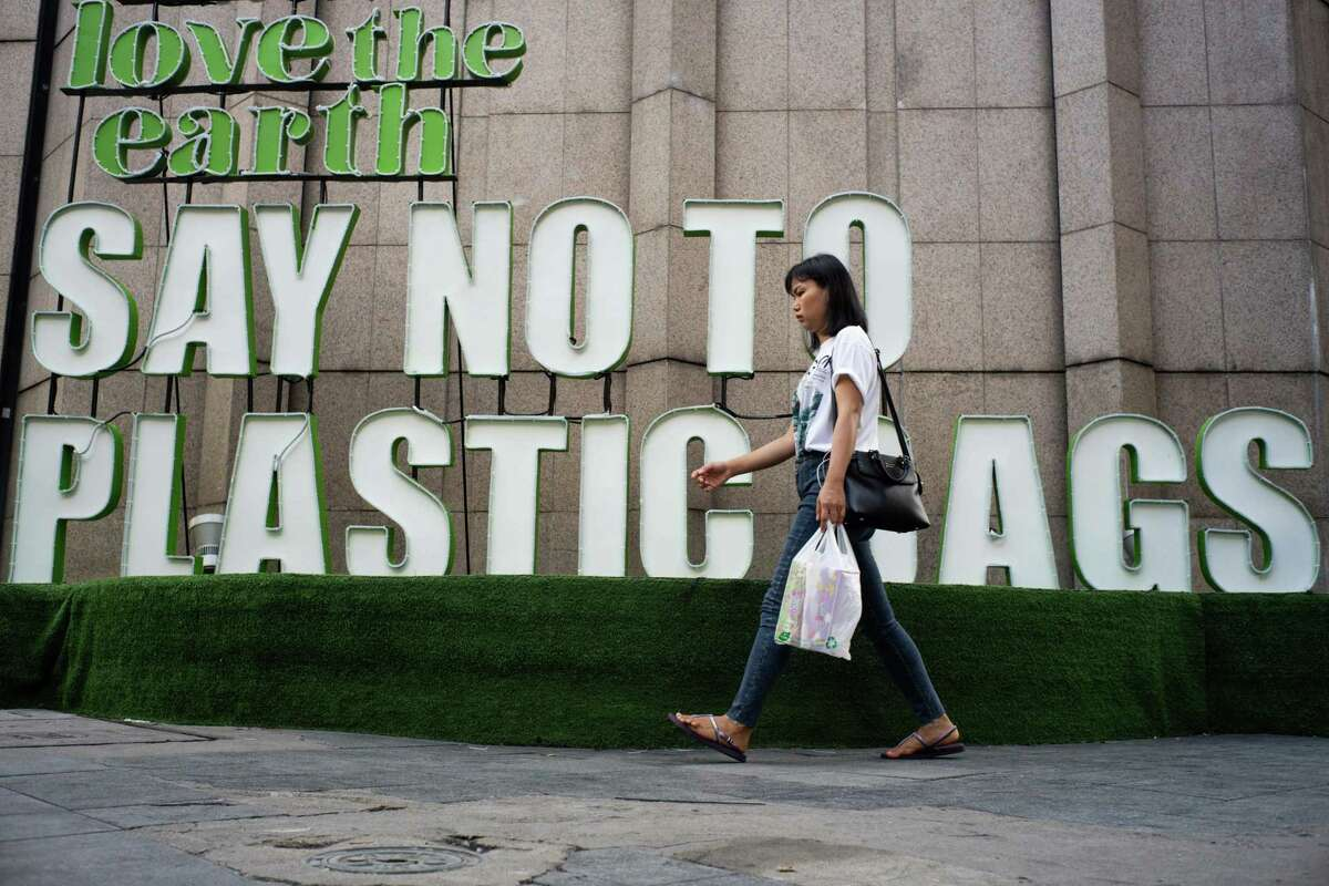 A woman walks past a sign reading 'Love the Earth Say No to Plastic Bags' in front of a shopping mall in Bangkok on June 7, 2019. (Photo by Jewel SAMAD / AFP)JEWEL SAMAD/AFP/Getty Images