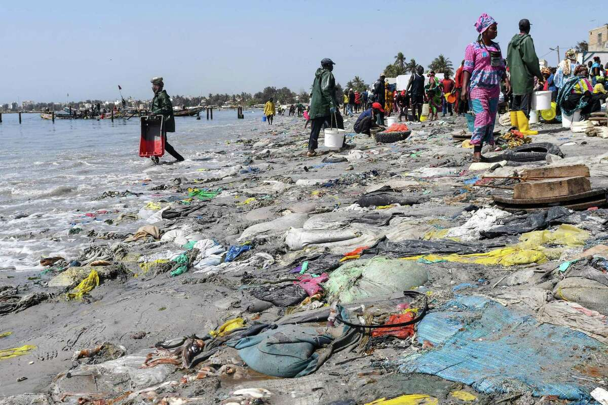 People walk near tires, plastic waste and dead fishes on June 1, 2019 in Dakar's highly populated Hann Bay. - Senegal's President Macky Sall launched a Zero Waste initiative to step up against the dumping of waste in public spaces. (Photo by Seyllou / AFP)SEYLLOU/AFP/Getty Images