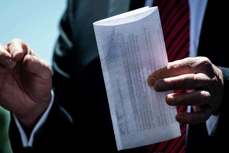 President Donald Trump holds up a page of what he says is an agreement between the United States and Mexico at the White House on Tuesday, June 11, 2019. Photo: Washington Post Photo By Jabin Botsford. / The Washington Post