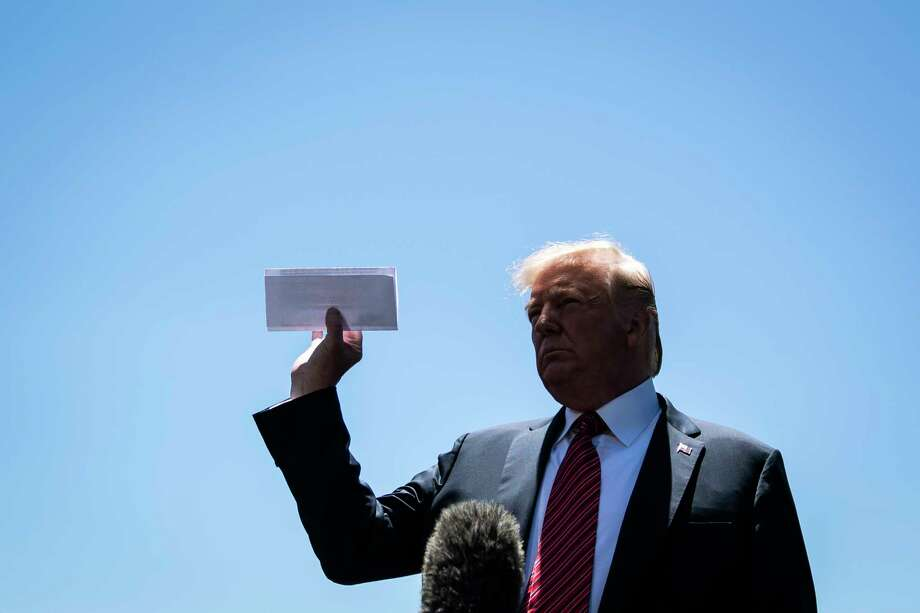 President Donald Trump holds up a page of an undisclosed agreement between the U.S. and Mexico on the South Lawn at the White House on Tuesday. Photo: Washington Post Photo By Jabin Botsford / The Washington Post