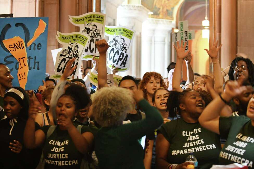 Environmental advocates occupy the Second Floor outside Gov. Andrew Cuomo's office on Tuesday, June 11, 2019, at the Capitol in Albany, N.Y. The group came to the Capitol is support of the Climate and Community Protection Act, a sweeping piece of state legislation aimed at addressing climate change by achieving zero carbon emissions and revamping the energy economy. Gov. Cuomo has been hesitant to support the CCPA. (Will Waldron/Times Union)