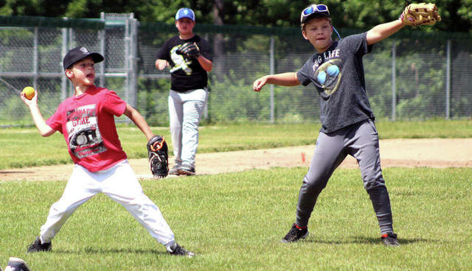A pair of Alton Redbirds Baseball Campers get set to throw the ball to first base, but only one, Carter Beran at left, has the ball during a scrimmage Tuesday at Alton High School. The camp runs through Wednesday. More photos can be found online at thetelegraph.com. Photo: Pete Hayes | The Telegraph
