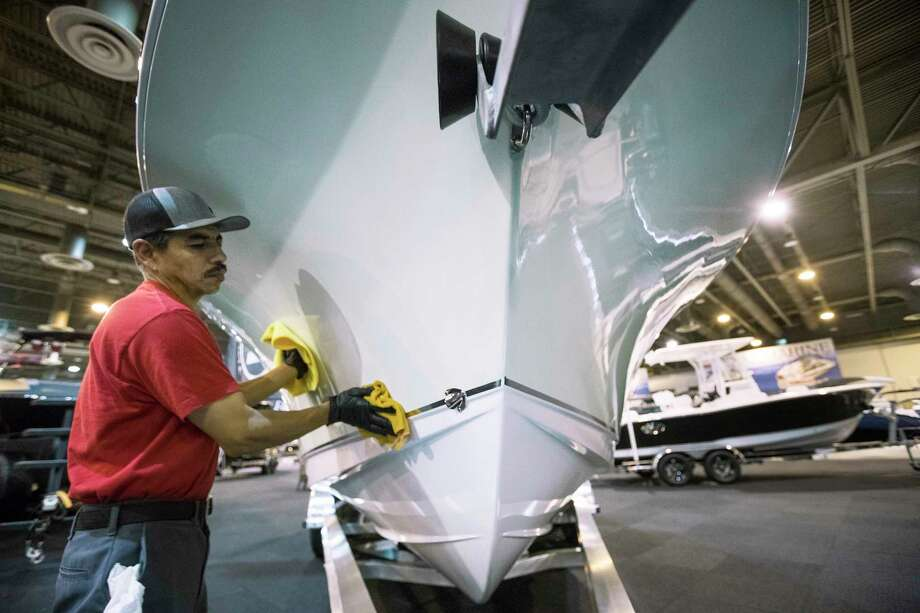 Leo Contreras shines the hull of a boat on display in the Rinker's Boat World area while preparing for the opening of the Houston Summer Boat Shows at NRG Center on Tuesday, June 11, 2019, in Houston. The show runs June 12-16. Photo: Brett Coomer, Staff Photographer / © 2019 Houston Chronicle