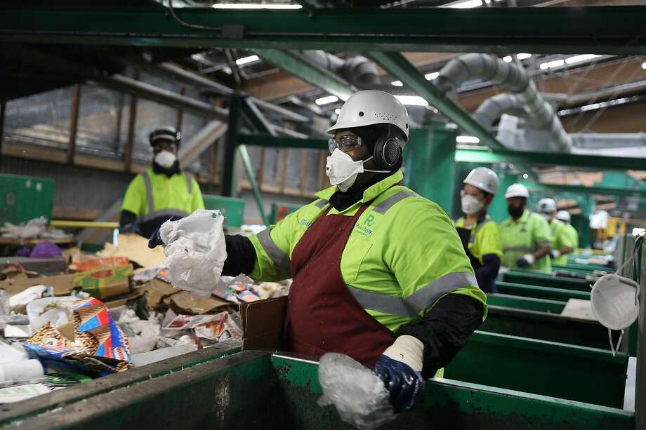 At Recology's initial sort deck, Tim Coleman separates out pieces of environment-unfriendly flimsy and film plastic destined for landfill. Photo: Lea Suzuki / The Chronicle