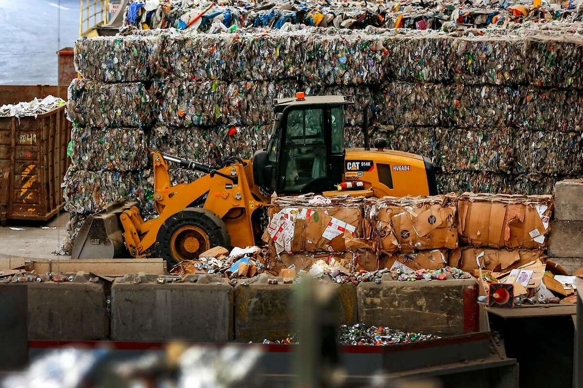 A wall of baled plastic sit behind a excavator in the back of the house at Recology's Recycle Central on Tuesday June 11, 2019 in San Fransisco, Calif. This wall is one day's worth of plastic and water bottles for San Fransisco.