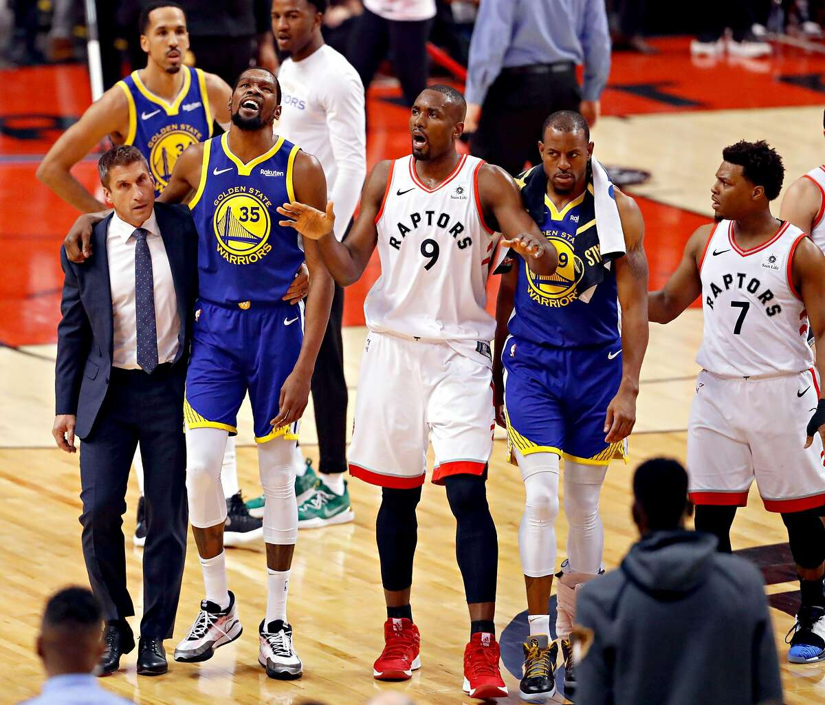 Golden State Warriors� Kevin Durant is helped off the court by the team�s director of sports medicine Rick Celebrini as Toronto Raptors� Serge Ibaka signals to the crowd in the first quarter during game 5 of the NBA Finals between the Golden State Warriors and the Toronto Raptors at Scotiabank Arena on Monday, June 10, 2019 in Toronto, Ontario, Canada.