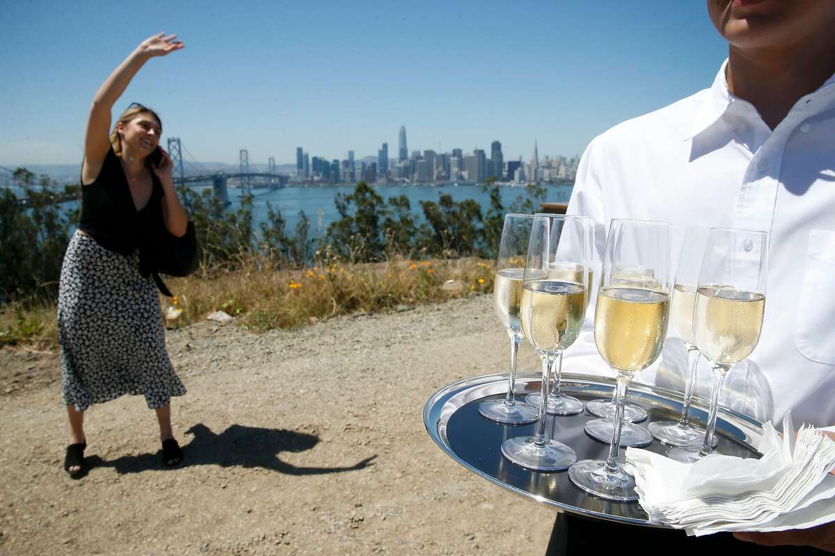 A waiter serves refreshments to guests invited to a groundbreaking ceremony for the construction of 266 residences and new neighborhood on Yerba Buena Island in San Francisco, Calif. on Tuesday, June 11, 2019.