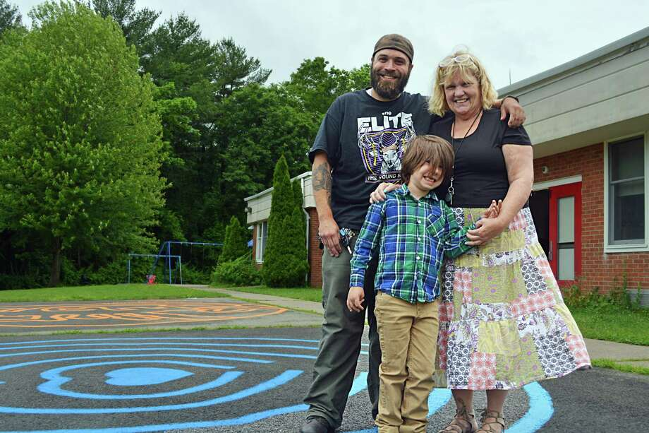Spencer School Elementary School kindergarten teacher Gretchen McInvale and building supervisor Jerry Flynn helped Middletown student Logan Murphy, 6, bring to life his complicated drawing of a labyrinth. The maze, painted on the playground along with a heart labyrinth created by McInvale, is used as a way to calm children who may be upset or antsy for activity. Photo: Cassandra Day / Hearst Connecticut Media