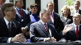 Gov. Greg Abbott, seated center, Lt. Gov. Dan Patrick, seated left, and Speaker of the House Dennis Bonnen, seated right, and other law makers attend a joint press conference to discuss teacher pay and school finance at the Texas Governor's Mansion in Austin, Texas, Thursday, May 23, 2019, in Austin. (AP Photo/Eric Gay)