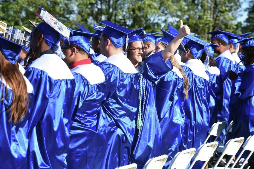 Kayla Manion gives the thumbs-up to her mother, grandmother and boyfriend as she takes her place during commencement exercises at West Haven High School Tuesday.