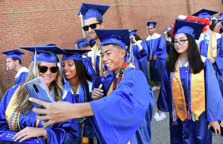 From left, Julia Walker, Lydia Abraham, Derek Baker and Joseph Delgado take a selfie at the beginning of commencement exercises at West Haven High School Tuesday.
