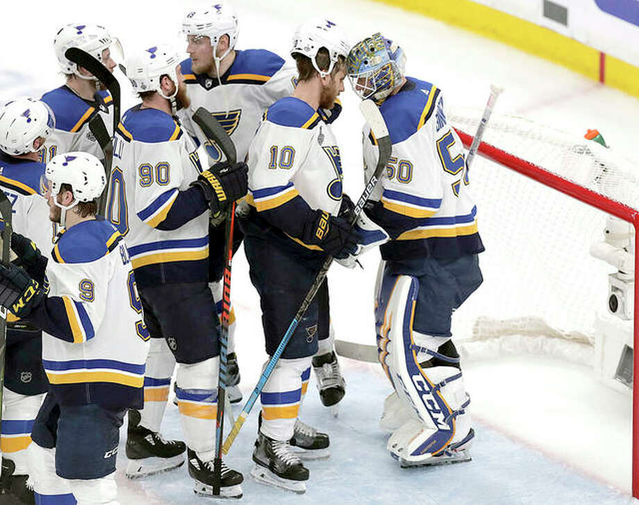 Blues teammates congratulate goaltender Jordan Binnington, right, after defeating the Bruins last Thursday in Game 5 of the Stanley Cup Final in Boston. Photo: AP Photo