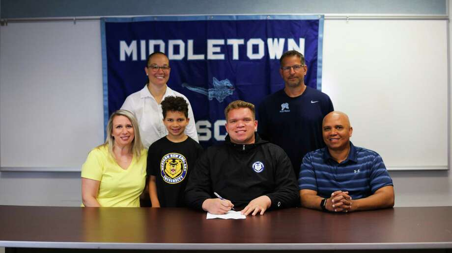 Middletown senior Cameron Barrett, seen with MHS athletic director Elisha DeJesus, coach Sal Morello and his family, will play football at Western New England College. Photo: Contributed / Calvin Ponzio