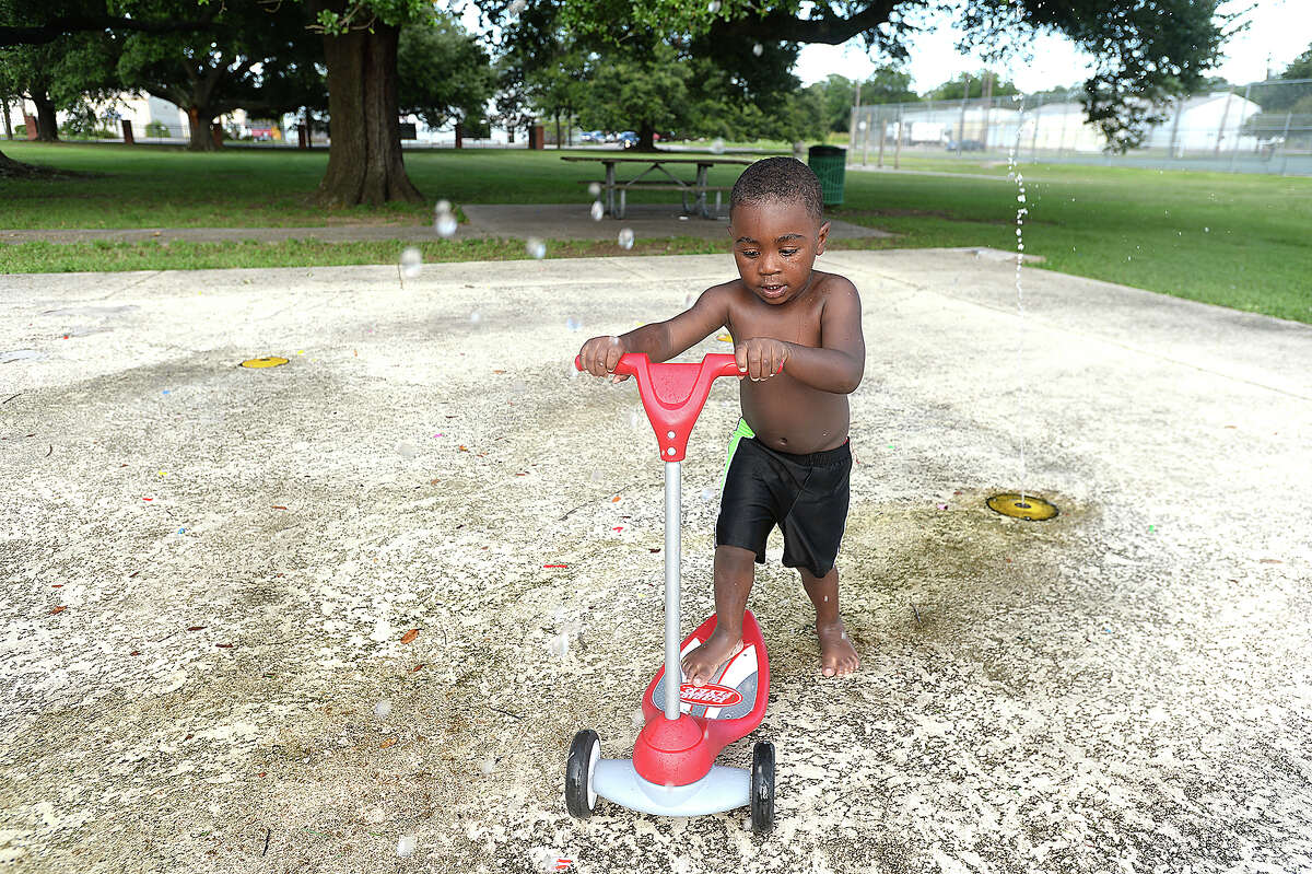 Lee Senegal rides his scooter through the splash pad as he and family play in Central Park Tuesday. Photo taken Tuesday, June 11, 2019 Kim Brent/The Enterprise
