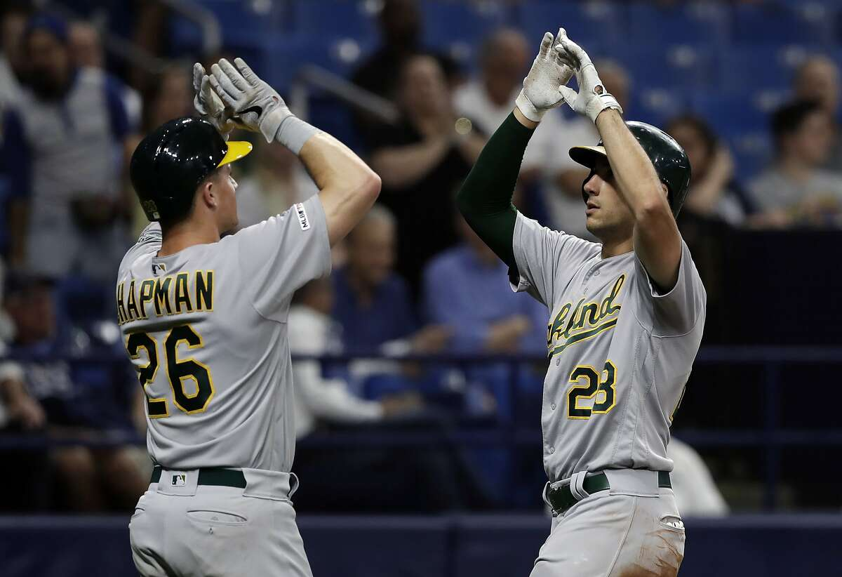 Oakland Athletics' Matt Olson, right, celebrates with Matt Chapman after Olson hit a two-run home run off Tampa Bay Rays relief pitcher Emilio Pagan during the sixth inning of a baseball game Tuesday, June 11, 2019, in St. Petersburg, Fla. (AP Photo/Chris O'Meara)