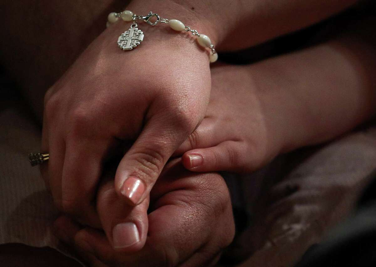 """Katie McNeese holds the hands of her husband Will McNeese, a pastor, and son Nate, 6, while praying on the first day of the Southern Baptist Convention's annual meeting on Tuesday, June 11, 2019, in Birmingham. """"More unity, for us to see the true reason why we're here and come together as a convention,"""" Katie McNeese said when asked what she wanted to see at this year's convention."""