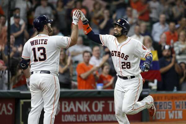 Houston Astros Robinson Chirinos (28) celebrates with Tyler White (13) after hitting his two-run home run during the seventh inning of an MLB baseball game at Minue Maid Park, Tuesday, June 11, 2019.