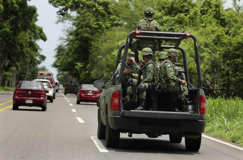 Soldados mexicanos están en la parte trasera de una camioneta mientras escoltan una caravana que transporta al Ministro de Defensa en Tapachula, México, el martes 11 de junio de 2019. Photo: Marco Ugarte /Associated Press / Copyright 2019 The Associated Press. All rights reserved.
