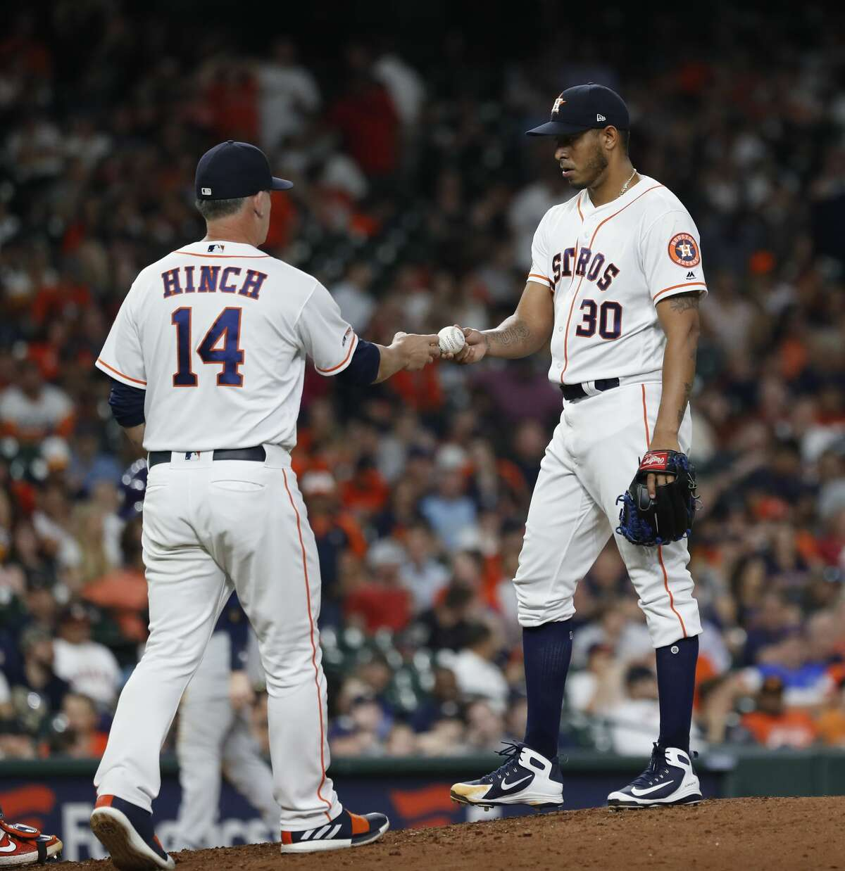 Houston Astros relief pitcher Hector Rondon (30) is pulled by manager AJ Hinch (14) after walking Milwaukee Brewers Travis Shaw with the bases loaded during the eighth inning of an MLB baseball game at Minue Maid Park, Tuesday, June 11, 2019.