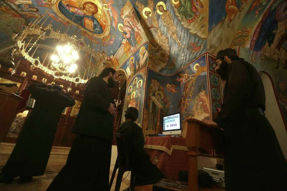 Greek Orthodox monks record a prayer on a computer in a church at Our Lady of Hamatoura Monastery in northern Lebanon on March 08, 2016.  The monastery's history goes back to the fifth century. It faced destructions and persecutions during the Mamluk and Ottoman eras and was restored in 1994. / AFP / PATRICK BAZPATRICK BAZ/AFP/Getty Images Photo: PATRICK BAZ, Stringer / AFP/Getty Images / AFP or licensors