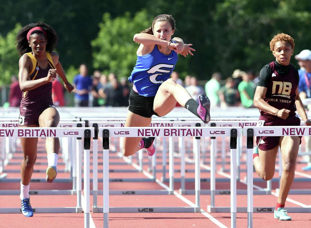 Tess Stapleton (center) of Fairfield Ludlowe runs to a first place finish in the 100 meter hurdles at the CIAC State Open Outdoor Track & Field Championship in New Britain on June 3, 2019.