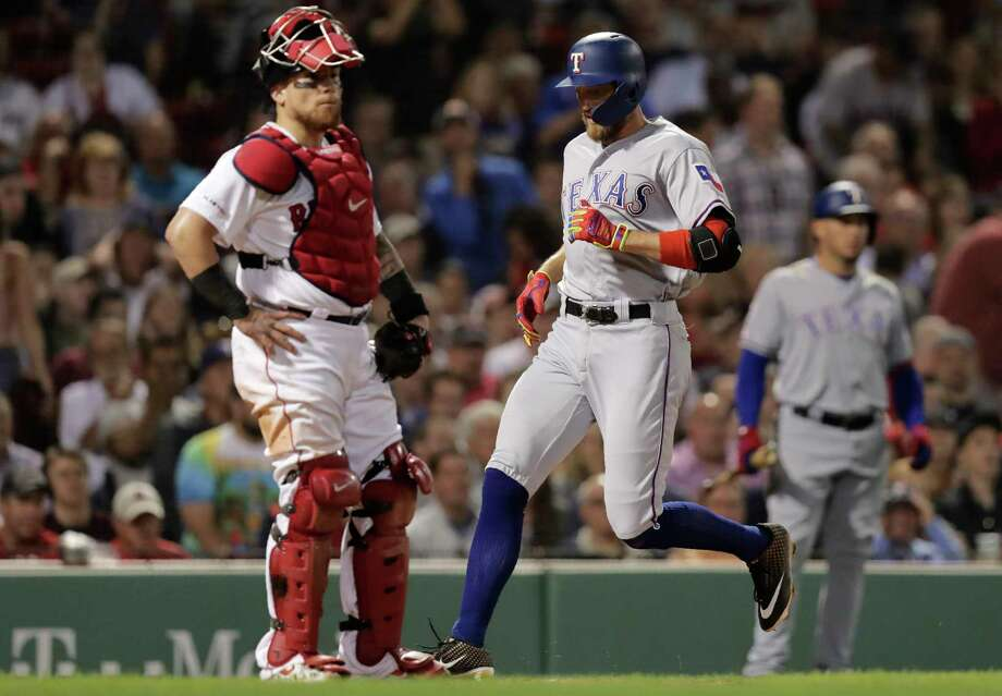 Texas Rangers' Hunter Pence, right, crosses home plate in front of Boston Red Sox catcher Christian Vazquez, left, while scoring on his inside the park home run in the sixth inning of a baseball game at Fenway Park in Boston, Tuesday, June 11, 2019. (AP Photo/Charles Krupa) Photo: Charles Krupa / Copyright 2019 The Associated Press. All rights reserved