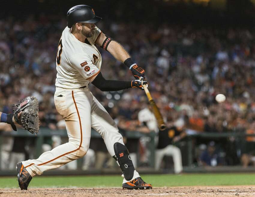 Giants' Evan Longoria hits a two-run double against the Padres in the seventh inning of a Giants win on a short sleeves night in San Francisco.