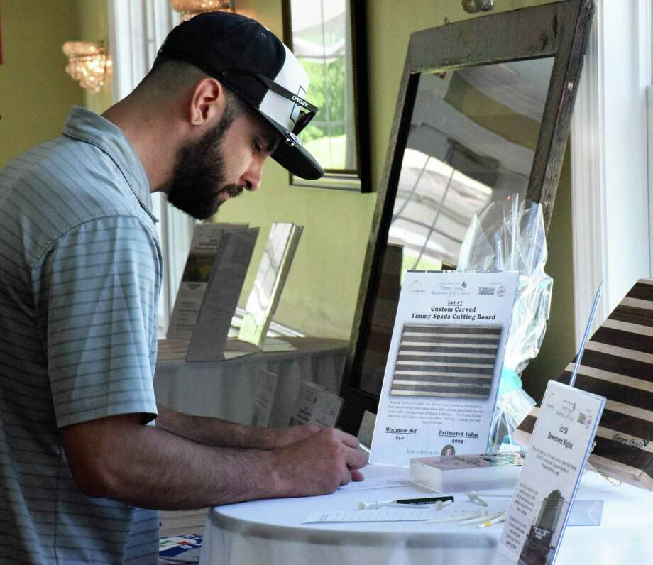 Spectrum/The fourth annual Timmy Spada Memorial Golf Classic was held at the Club at River Oaks June 3, 2019. The tournament is held in memory of Timmy Spada, a New Milford High School graduate who died in 2015. Above, Joe Casanova of New Milford, stepson of Jim Spada, peruses the array of auction items during the reception post-tournament. Photo: Deborah Rose / Hearst Connecticut Media / The News-Times  / Spectrum