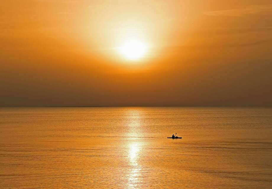 A kayaker was recently spotted cruising along the shore, near Sleeper State Park, as the sun set over Lake Huron. Photo: Bill Diller/For The Tribune