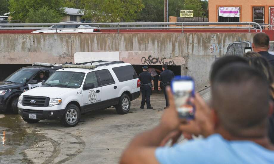 Onlookers watch as the Webb County Medical Examiner's office and Laredo Police respond to a call of a dead body found under a bridge on the 4500 block of McPherson Avenue. Photo: Danny Zaragoza/Laredo Morning Times