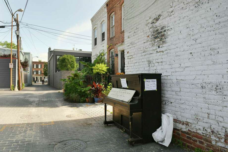"""An abandoned piano sits in a Capitol Hill alley, free for the taking, on May 21, 2019. Its sign says """"Free piano - please take and enjoy - Otherwise bulk trash will haul away, Thank you."""" Photo: Washington Post Photo By Katherine Frey / The Washington Post"""