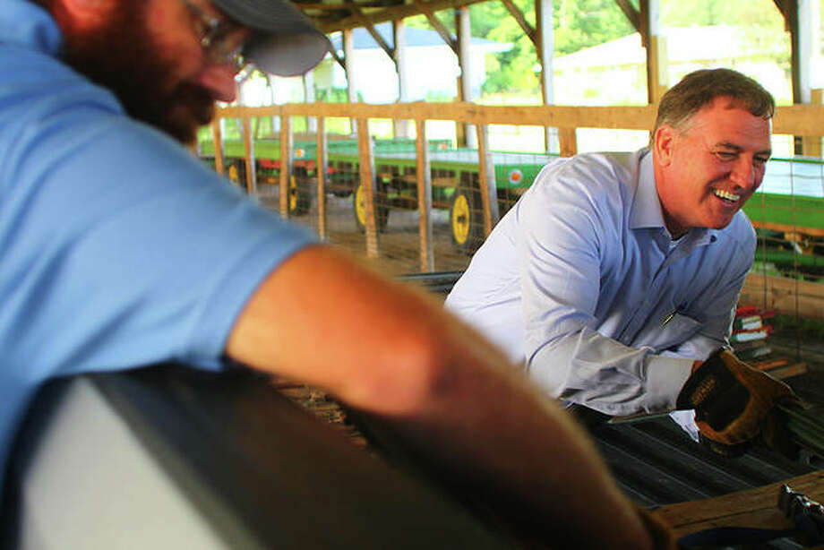 Doug Coop (left) helps John Sullivan, director of Illinois Department of Agriculture and a Rushville farmer, unload fencing supplies Tuesday at the Morgan County fairgrounds. The supplies will be added to those being sent to Nebraskan farmers. Photo: Rosalind Essig | Journal-Courier