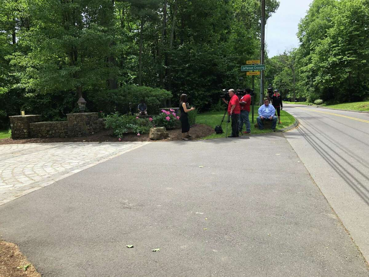 Members of the media gather at the entrance to Jefferson Crossing, a private Farmington road lined with multimillion dollar homes built by Fotis Dulos' company, the Fore Group.