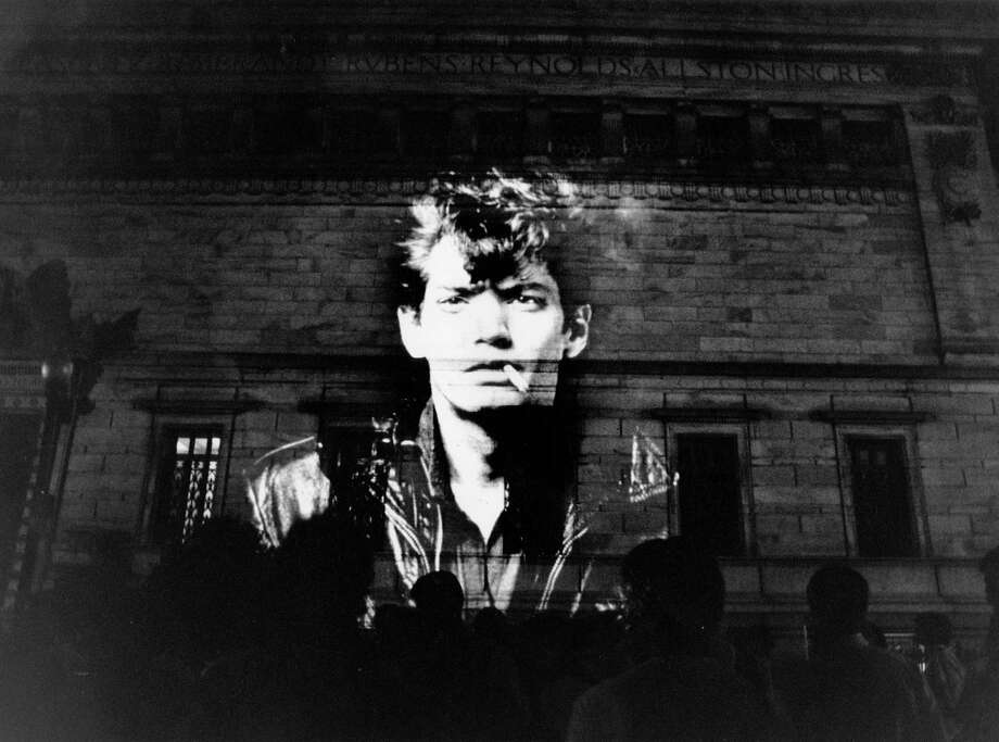 A Robert Mapplethorpe self-portrait is projected on the Corcoran Gallery of Art during a 1989 protest over trustees' decision not to show his work. Photo: Washington Post Photo By Carol Guzy / The Washington Post